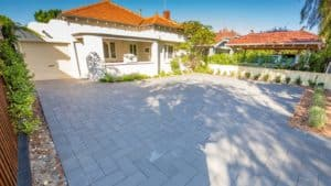 Photo of a large driveway made with pavers in front of a white house