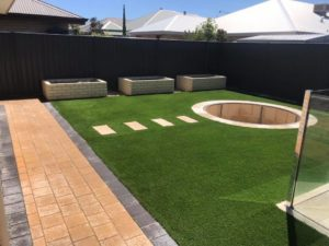 Photo of a backyard landscape with fresh green grass and a round firepit in the middle